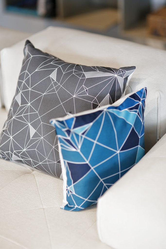 Almofadas nas cores azul e cinza sobre um sofá bege: mais uma dica simples de decoração