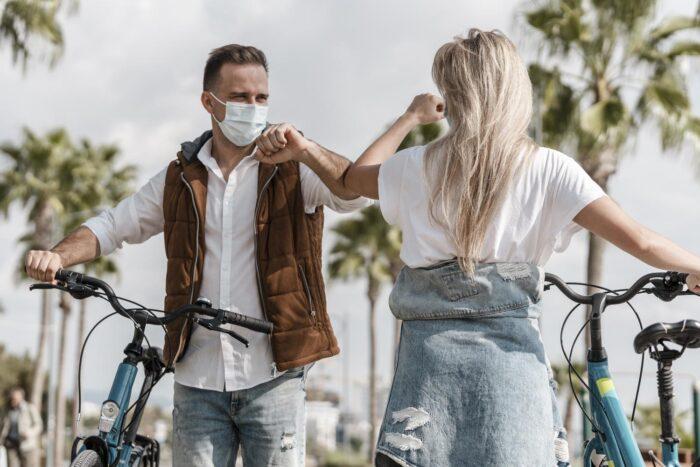 homem e mulher com máscara se cumprimentam com o cotovelo. Eles estão de bicicleta.