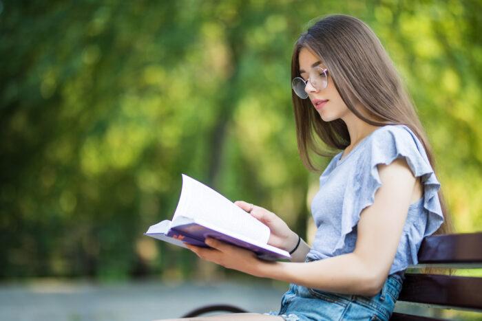 garota de óculos e blusa azul sentada ao ar livre lendo um livro